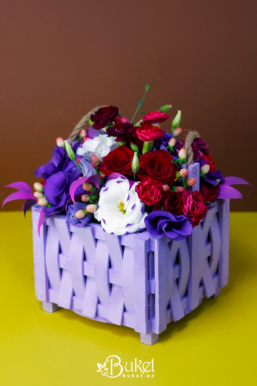 Composition in a wooden basket of roses and irises